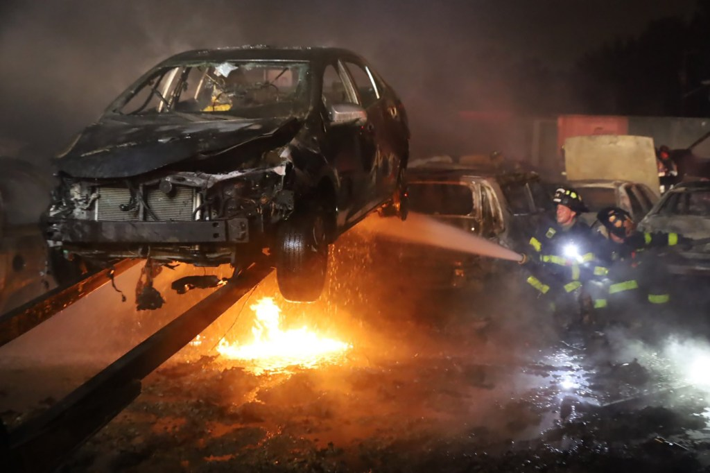 Firefighters extinguish cars from the massive flames.