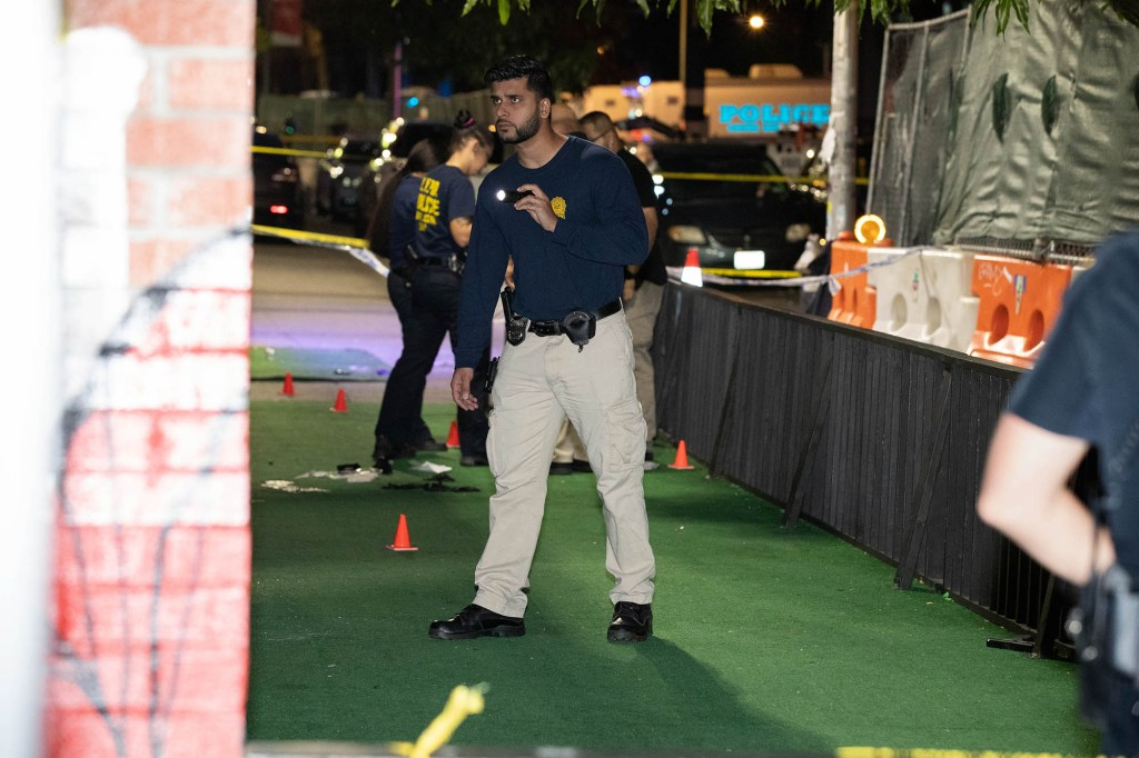 An officer investigates at the scene of the shooting.