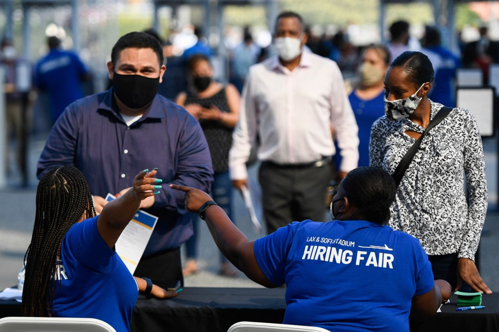 People receive information as they attend a job fair for employment with SoFi Stadium