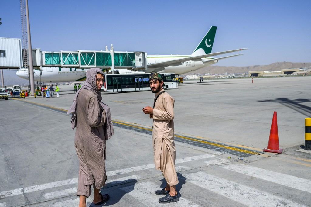 Taliban fighters patrol Kabul's airport as Pakistan International Airways plane boards several refugees.