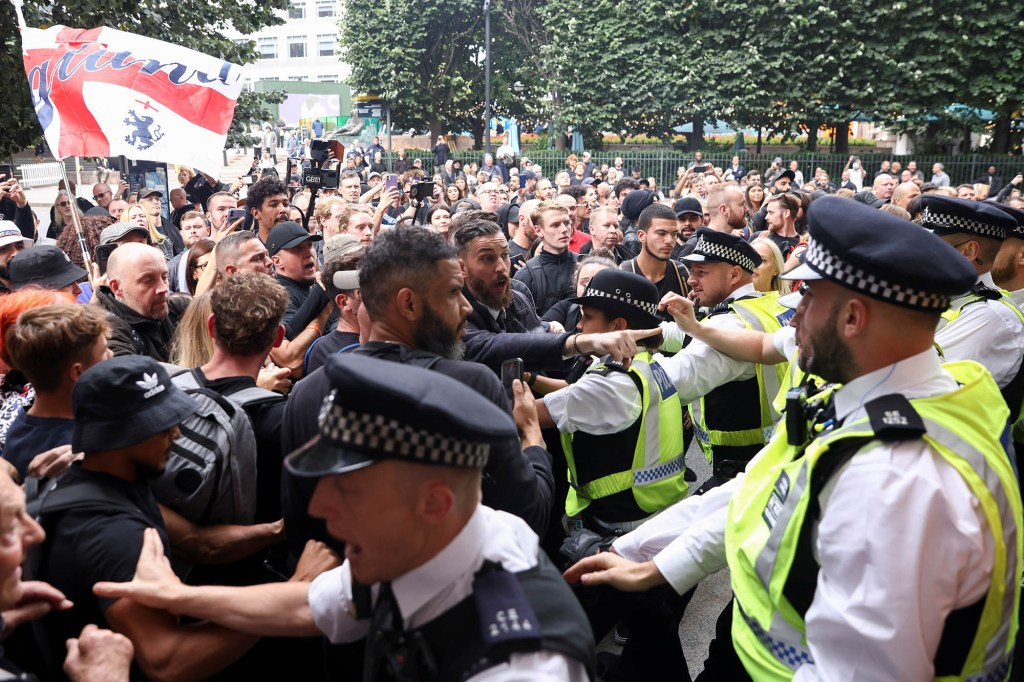 Members of the Official Voice group scuffle with police officers.