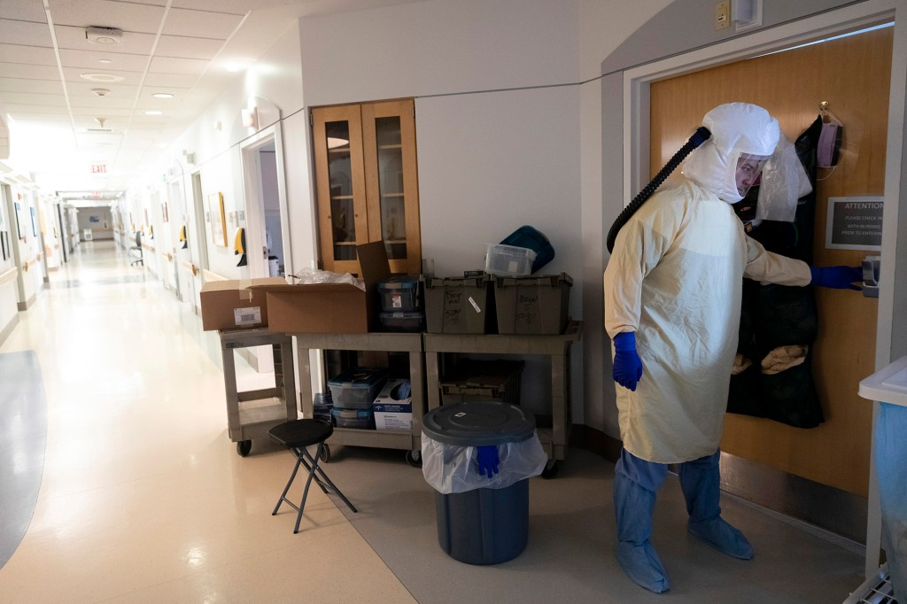 Charge nurse Matthew Paré  leaves the room of a patient who is being tested for coronavirus in full personal protective equipment (PPE) at Maine Medical Center on Wednesday, March 11, 2020.