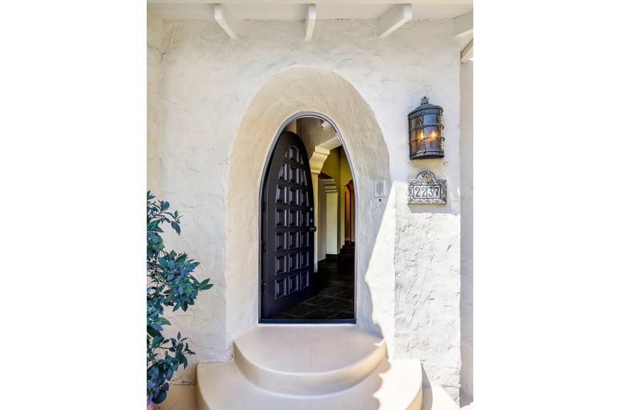The arched doorway hosts a carved wood door.