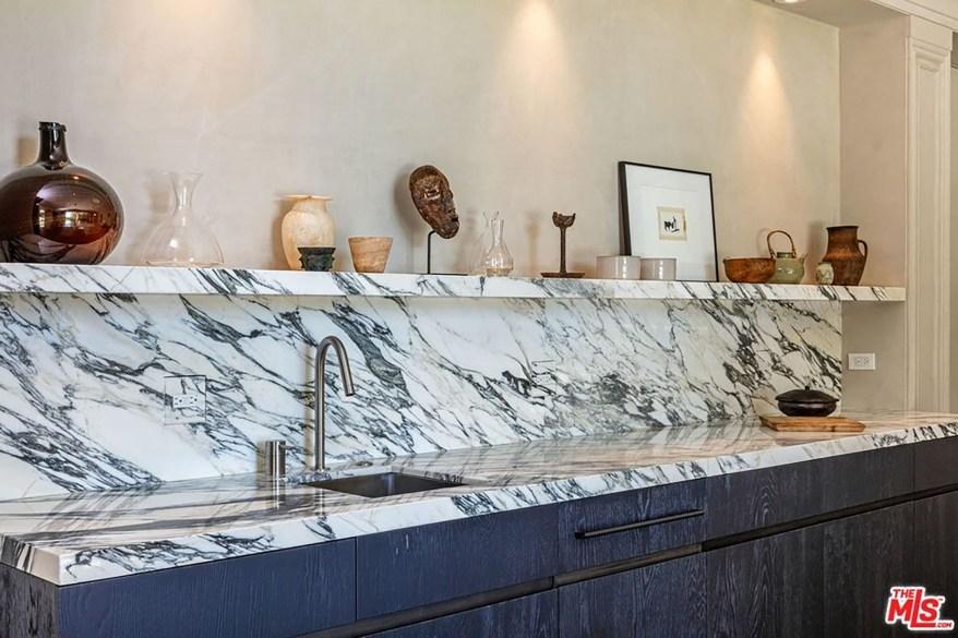 Knick knacks top the marble kitchen backsplash.
