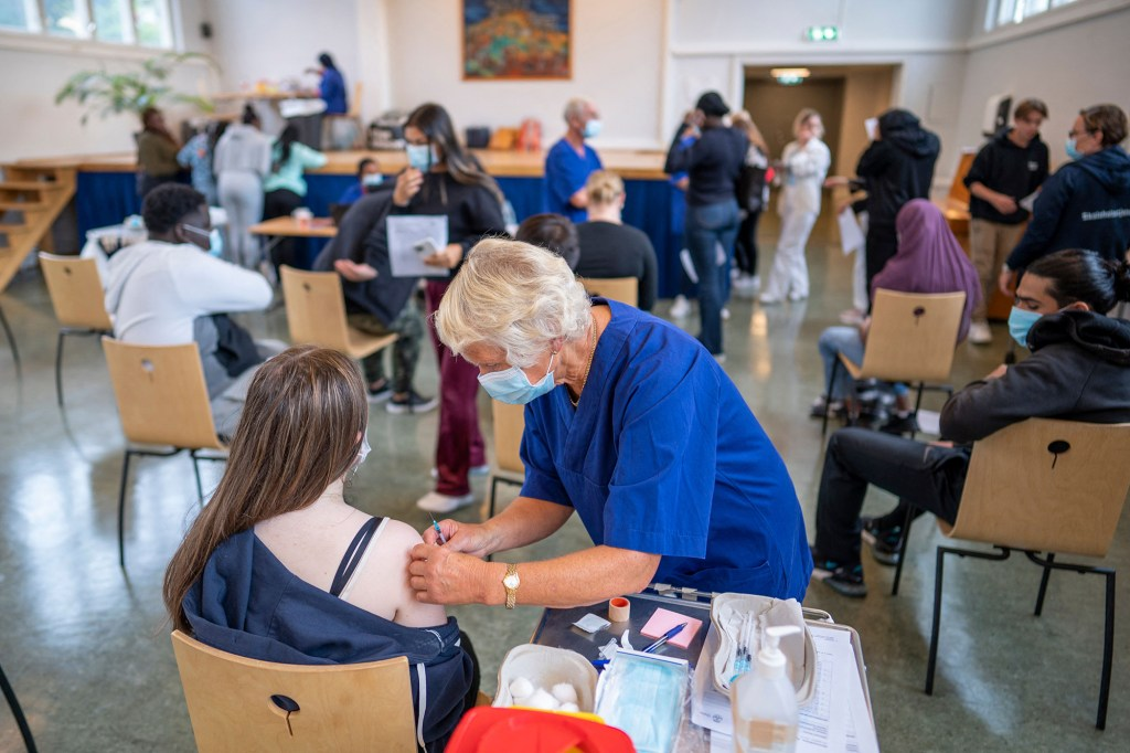 A student at Holtet high school in Oslo receives the first dose of Pfizer vaccine against covid-19 in the school's auditorium on September 7, 2021.