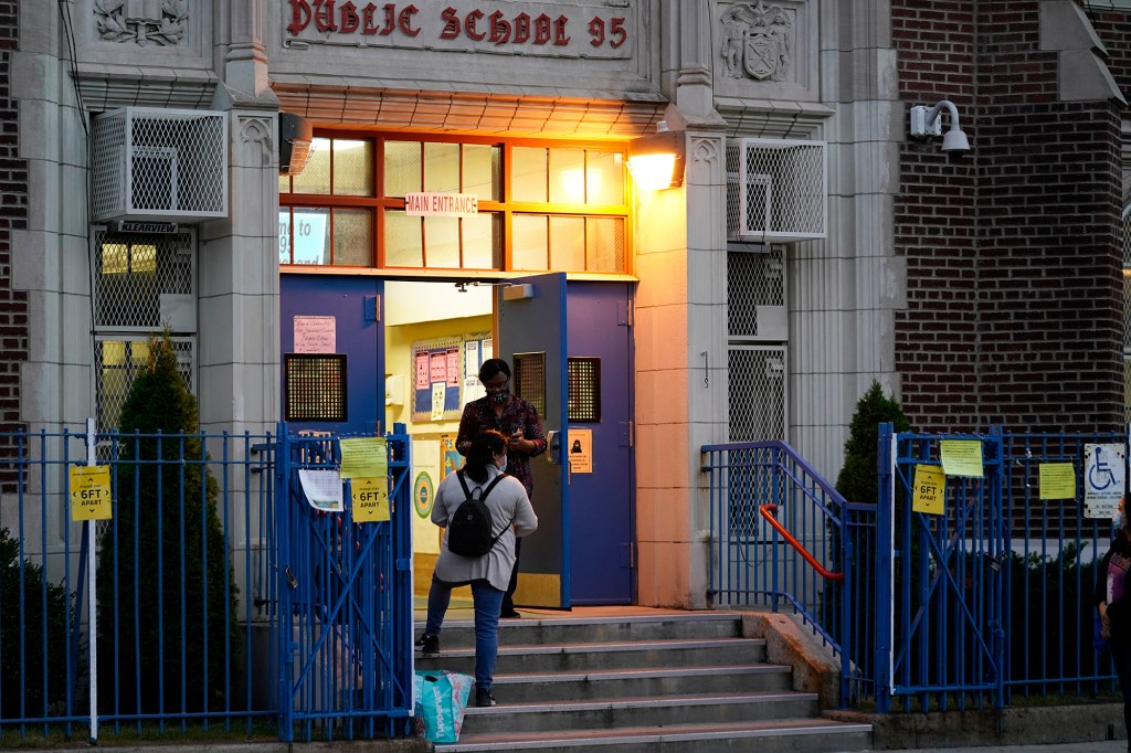 A Department of Education employee talks to a parent on the steps outside Public School 95 in Brooklyn's Gravesend neighborhood Monday, Oct. 5, 2020
