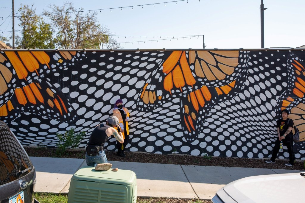 People taking photos at the Monarch Mural in Ogden, Utah that Petito once posed at before disappearing.