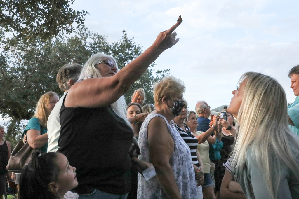 A mourner releasing a butterfly in honor of Petito at the vigil.