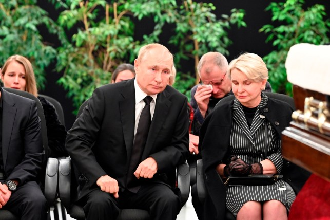 Russian President Vladimir Putin sits with Natalia Zeni-Shiva, the widow of Eugene Zeni-Chev, Russia's Minister of Emergency Situations, who died while on duty during inter-agency exercises to save the Arctic zone. Save the person's life.