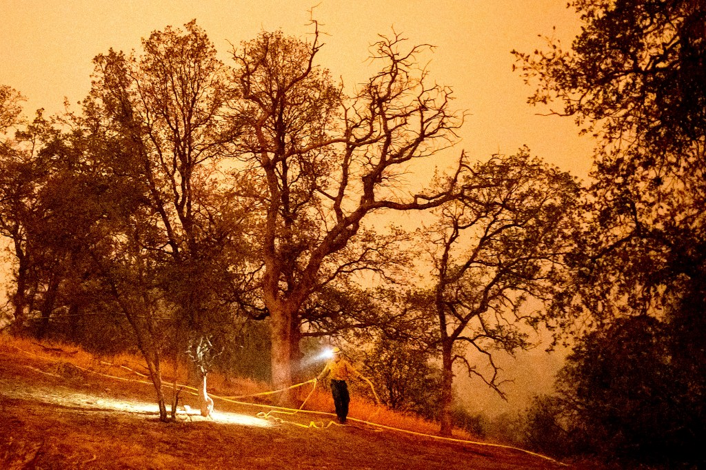 A firefighter lays hose around the Foothills Visitor Center while battling the KNP Complex Fire in Sequoia National Park, Calif.