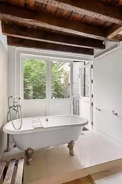 This bathroom has a standalone tub and a view of the courtyard.