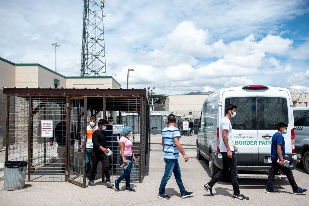 Recently-apprehended migrants are guided out of the El Paso Del Norte Processing Center in El Paso, Texas.