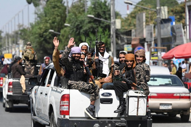 Taliban fighters wave as they patrol in a convoy along a street in Kabul