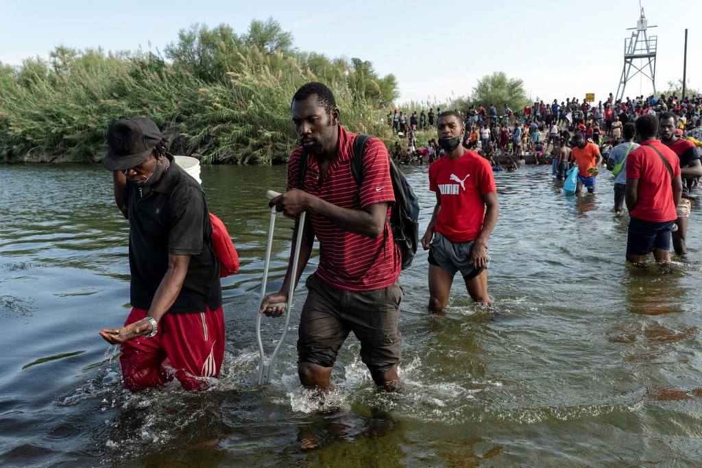 Migrants seeking asylum in the U.S. walk in the Rio Grande river near the International Bridge between Mexico and the U.S. as they wait to be processed, in Del Rio, Texas,
