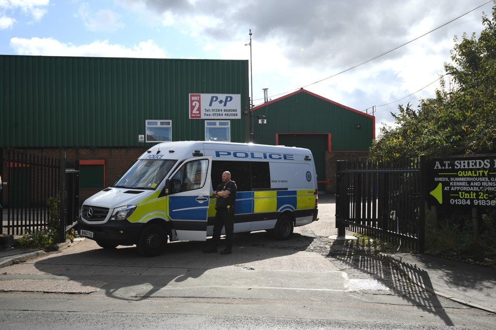 A police vehicle blocking an entrance to Albion Works industrial estate in Brierley Hill, West Midlands, in the area where two men were found shot dead in a car.