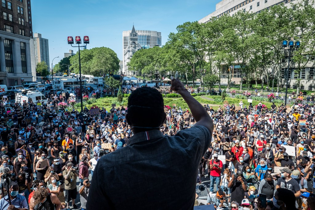 Advocate Jumaane D. Williams raises his hand as he speaks to a crowd of thousands at Brooklyn Borough Hall.