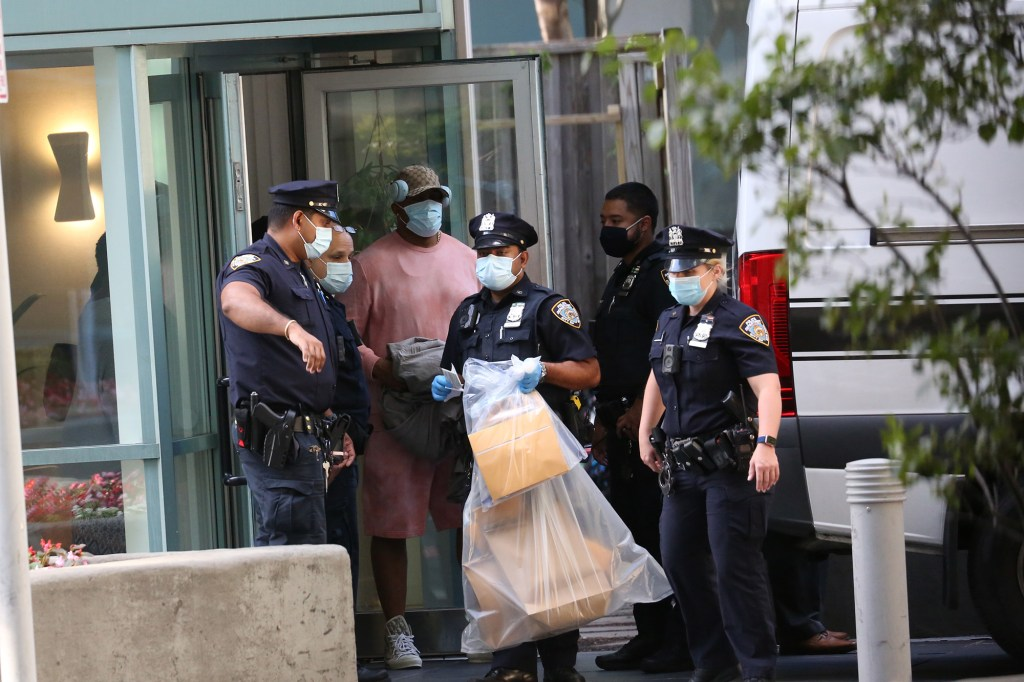 NYPD officers carrying evidence out of Williams' building.