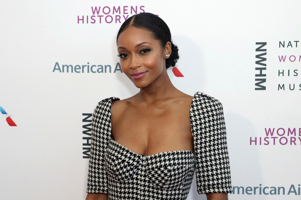 Yaya DaCosta smiles at the camera while wearing a black and white dress