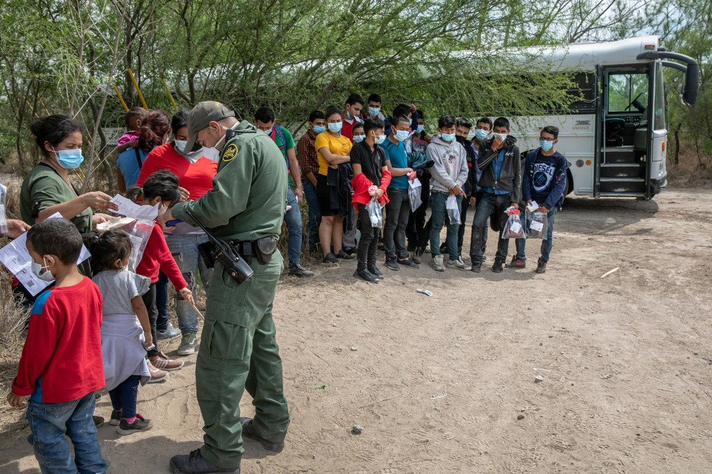 A U.S. Border Patrol agents questions families, as a group of unaccompanied minors (R), looks on after they crossed the Rio Grande into Texas on March 25, 2021 in Hidalgo, Texas.