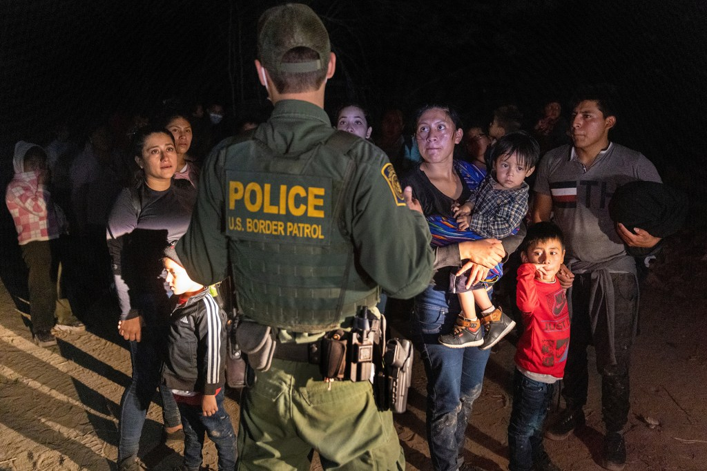 Immigrants wait for a U.S. Border Patrol agent to lead them up from the bank of the Rio Grande after they crossed the U.S.-Mexico border on April 14, 2021 in Roma, Texas.