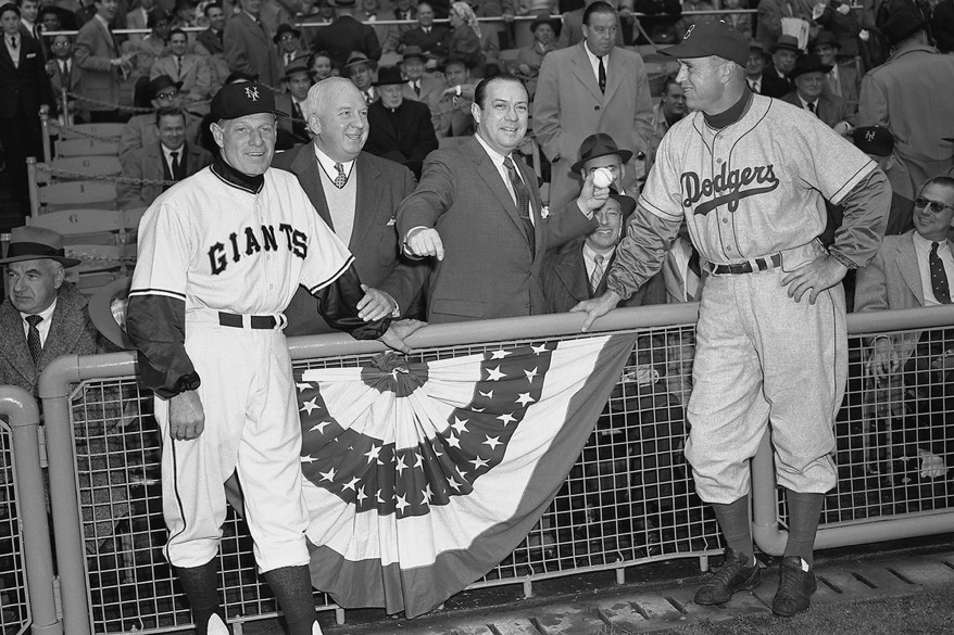 Manager Leo Durocher, of the New York Giants, National League President Warren Giles, New York City Mayor Robert Wagner, Jr., and manager Walt Alston, of the Brooklyn Dodgers, pose for a portrait as Mayor Wagner prepares to throw out the ceremonial first pitch prior to the Opening Day game on April 14, 1955 at the Polo Grounds in New York, New York.