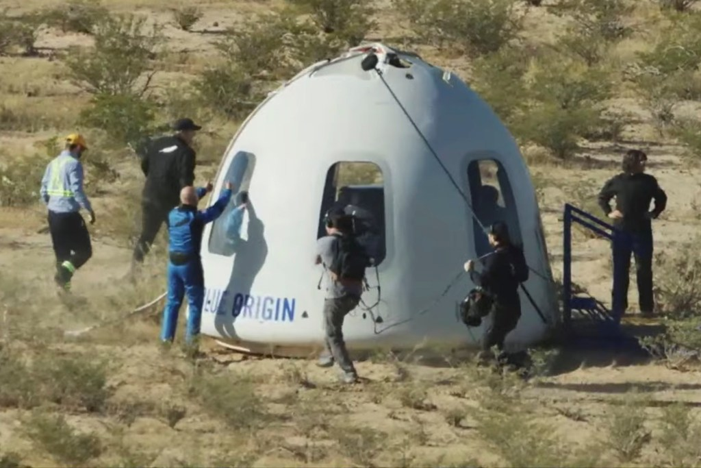 Billionaire Jeff Bezos gives a thumbs-up outside the capsule of Blue Origin's New Shepard which carried actor William Shatner to space.