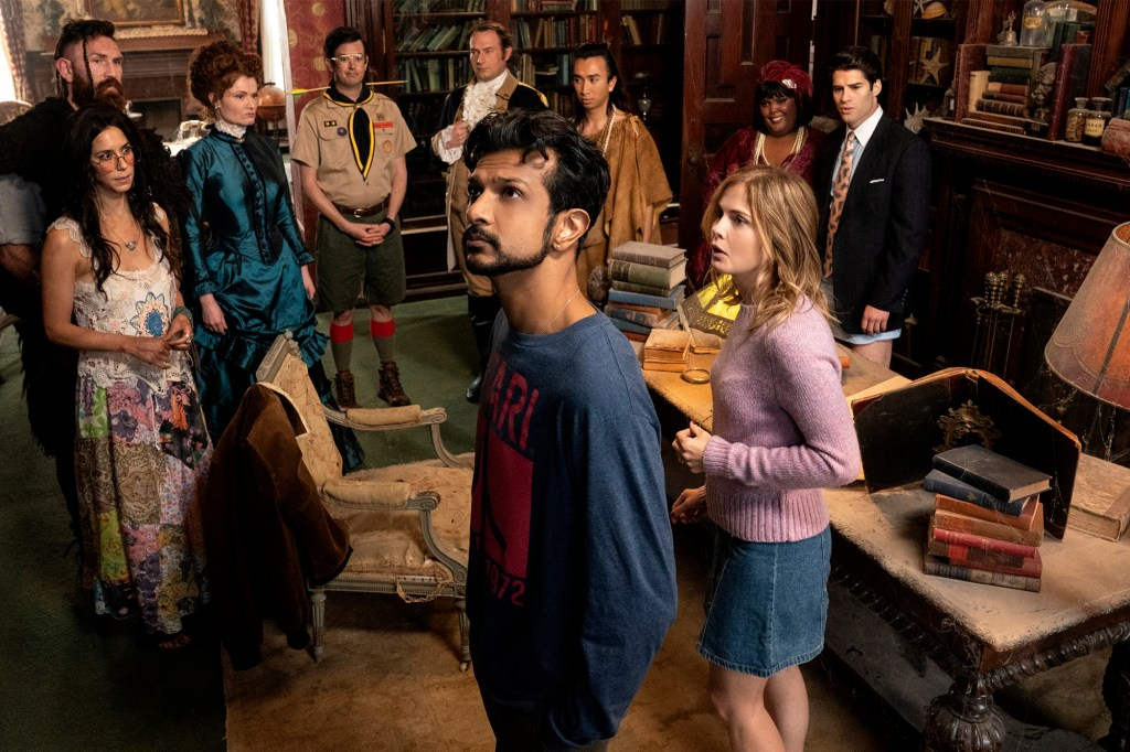 Utkarsh Ambudkar as Jay  and Rose McIver as Samantha, stand in a room surrounded by ghosts:  Sheila Carrasco as hippie Flower (back left), Devan Chandler Long as Viking Thorfinn, Rebecca Wisocky as Hetty,  Richie Moriarty as Pete, Brandon Scott Jones as Isaac,  Romn Zaragoza as Sasappis, Danielle Pinnock as Alberta and Asher Grodman as Trevor