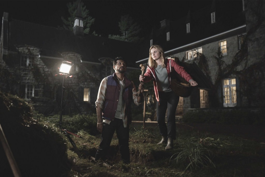 Jay (Utkarsh Ambudkar) and Samantha (Rose McIver), right, stand outside digging a large hole in the ground.