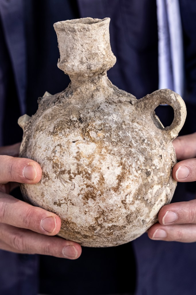 An Israel Antiquities Authority employe holds a jar from a massive ancient winemaking complex dating back some 1,500 years in Yavne, central, Israel, Monday, Oct. 11, 2021.