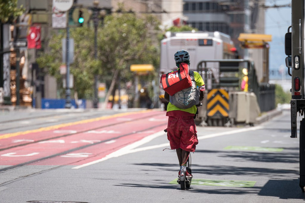 A Grubhub delivery worker riding on a scooter.