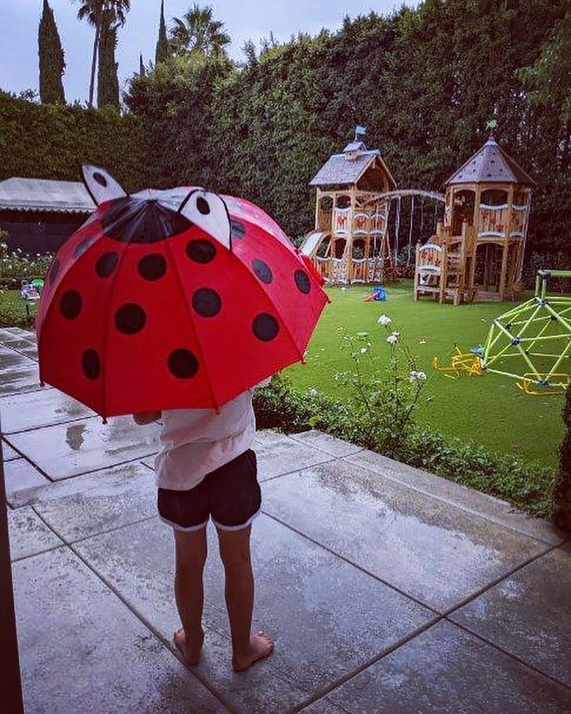 """""""When it rained for that very short amount of time, it was the most exciting thing that ever happened in our house,"""" she captioned a picture of her daughter looking out over the play set from under a ladybug umbrella."""
