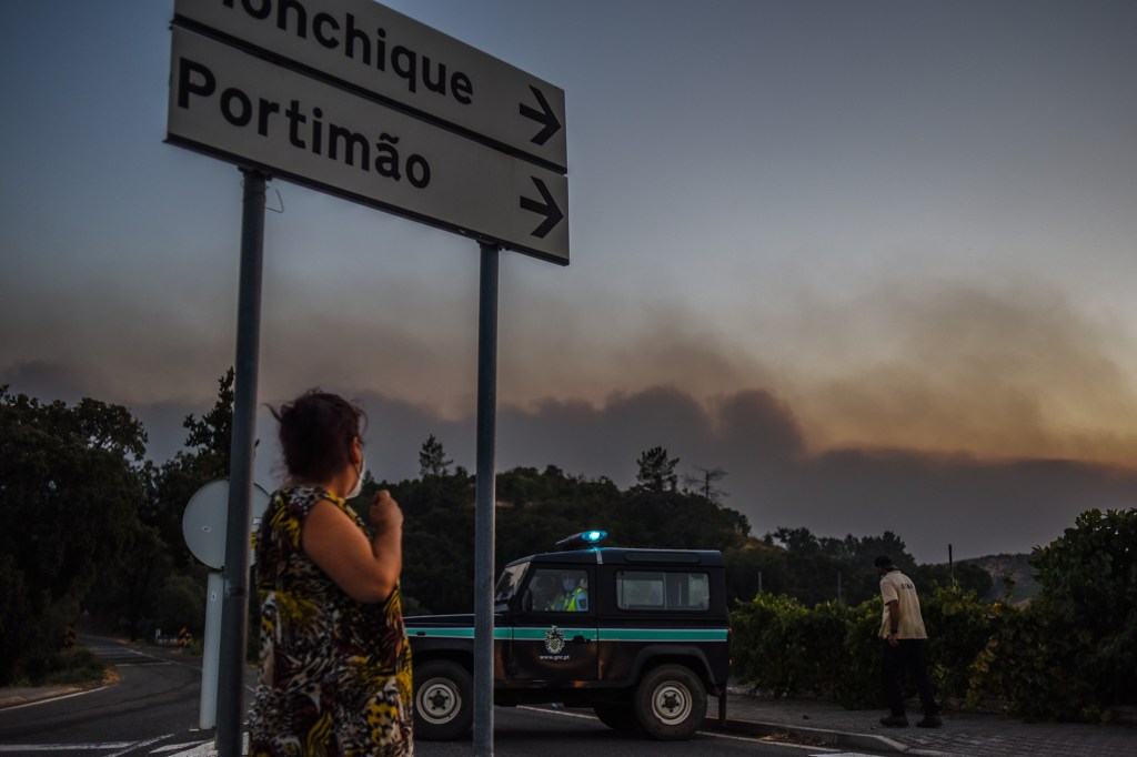A woman wears a protective face mask and stands next to a road sign as the National Republican guard blocks a road due to an ongoing wildfire in Odemira district on August 18, 2021 in Odemira, Portugal. Fires have broken out in the cork, eucalyptus and pine forests of the Odemira municipality of Portugal after prolonged periods of dry, hot weather.