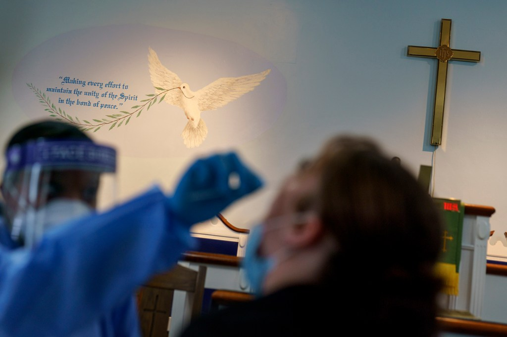 A mural and a cross decorate the wall of Bethel AME Church as a testing assistant conducts a COVID-19 test at a clinic set up in the sanctuary as part of an effort to make testing and vaccines more available to an underserved community, Friday, Sept. 24, 2021, in Providence, R.I.