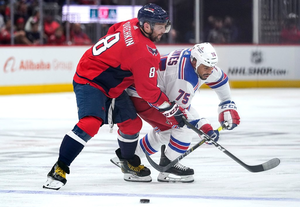 Alex Ovechkin keeps the puck away from Ryan Reaves during the Rangers' 5-1 opening-night loss to the Capitals.