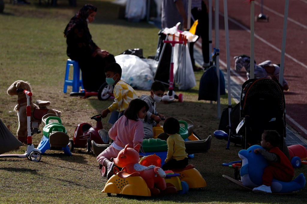 """Family members of some 390 Afghans, who were airlifted from Kabul to South Korea as """"persons of merits"""" on August 26, at the National Human Resources Development Institute playground on Jincheon in Chungcheongbuk-do Province, south of Seoul, South Korea, October 13, 2021."""