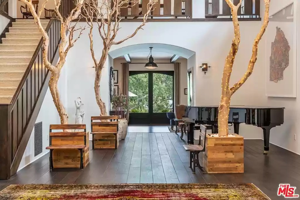 The dramatic entryway is positioned with trees, showing off the height of the ceiling.