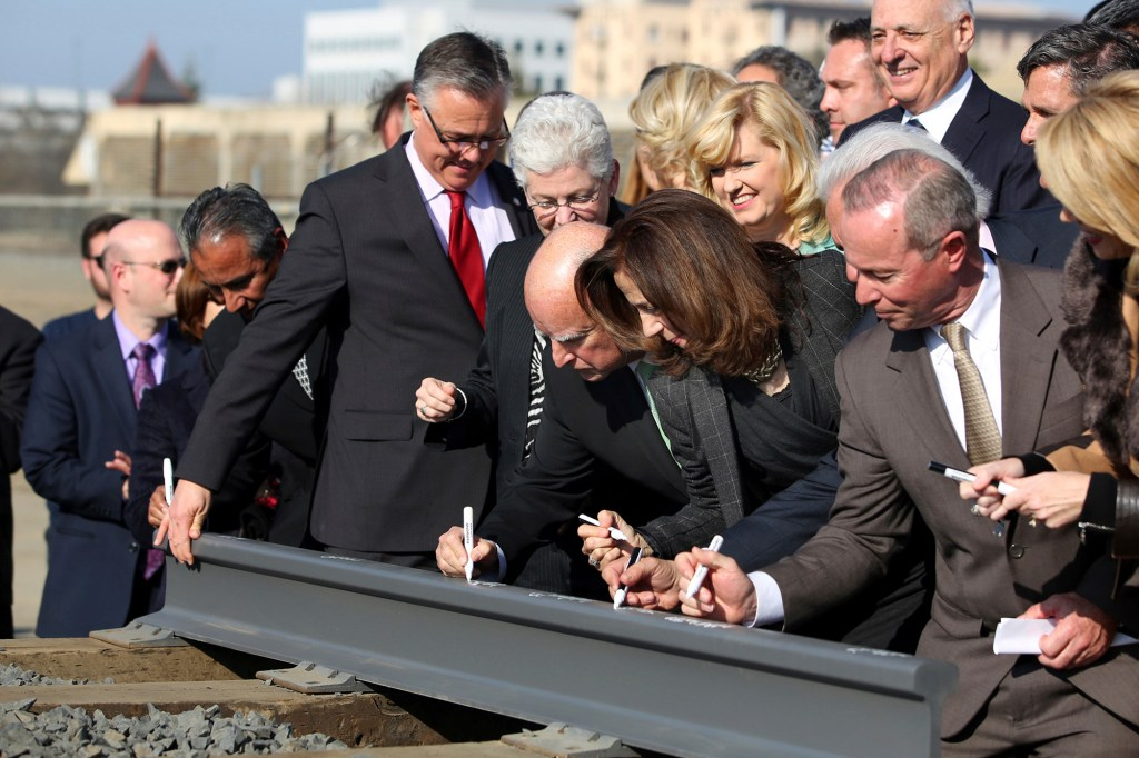 In this June. 18, 2015 file photo, Gov. Jerry Brown, center, and his wife, Anne Gust Brown, fourth from right, sign a portion of a rail at the California High-Speed Rail Authority in Fresno, Calif.