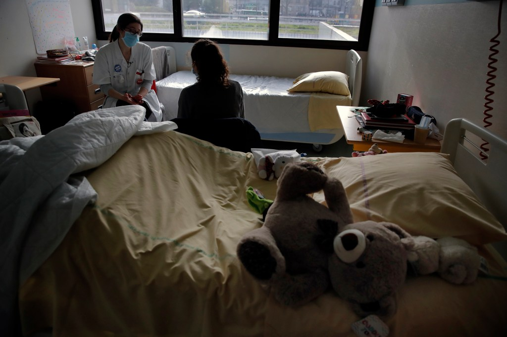In this Tuesday, March 2, 2021 file photo, psychiatrist Coline Stordeur speaks with a young girl in her room in the pediatric unit of the Robert Debre hospital, in Paris, France.
