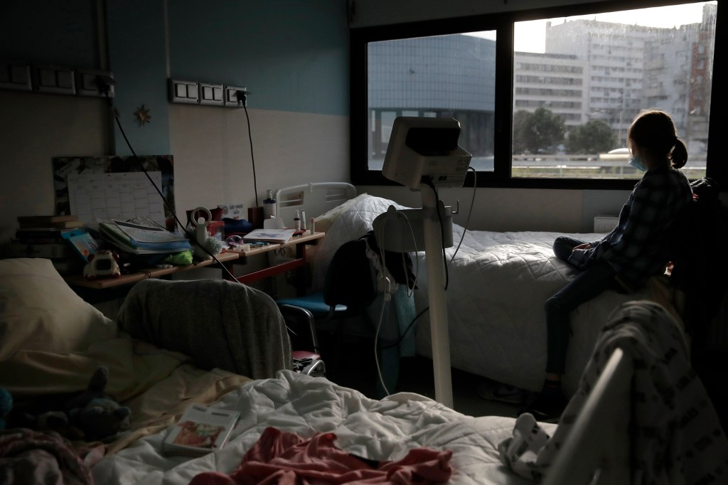 In this Tuesday, March 2, 2021 file photo, a young girl looks out the window of her room in the pediatric unit of the Robert Debre hospital, in Paris, France.