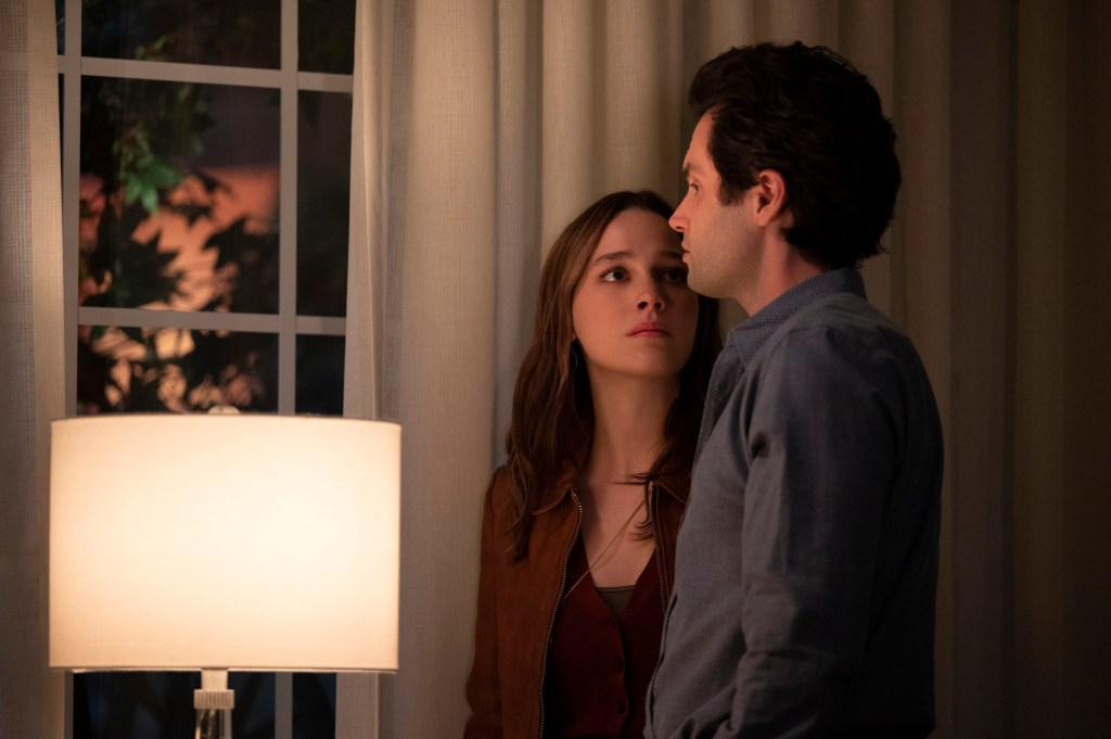 Love (Victoria Pedretti) and Joe (Penn Badgley) stand in a living room in front of a window next to a lamp, while Love looks into Joe's face and Joe looks out the window.