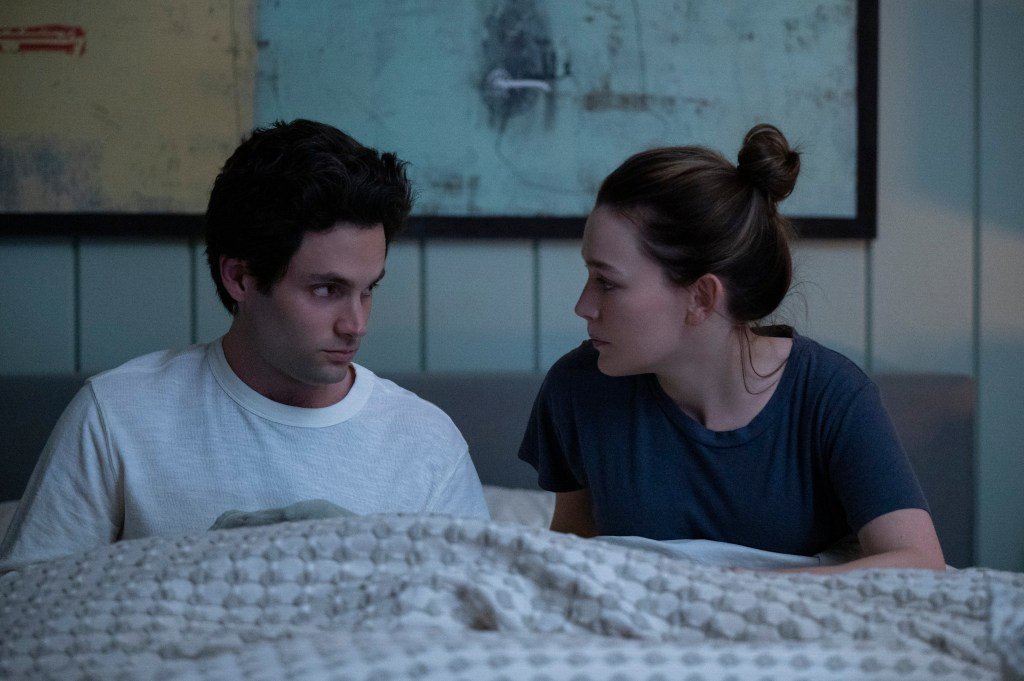 """Joe (Penn Badgley), left, and Love (Victoria Pedretti) sit in bed together side by side, looking at each other, unsmiling, in """"You"""" Season 3."""