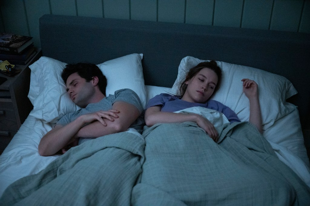 Joe (Penn Badgley), left, and Love (Victoria Pedretti) lie in bed together side by side, sleeping.