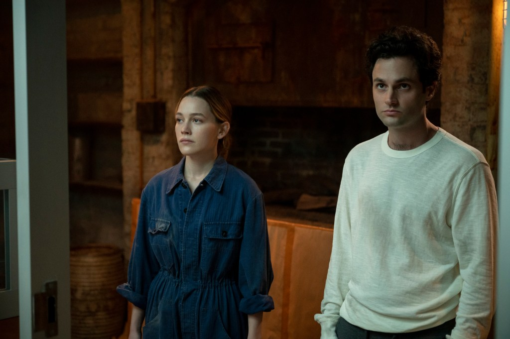 """Love (Victoria Pedretti), left, and Joe (Penn Badgley) stand side by side, unsmiling, in """"You"""" Season 3."""