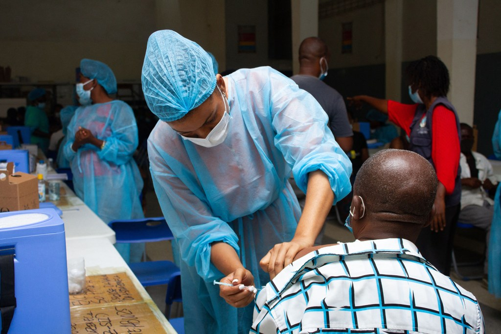 Nurses administer jabs as Angolans queue to receive a Covid-19 vaccination in Luanda on October 1, 2021.