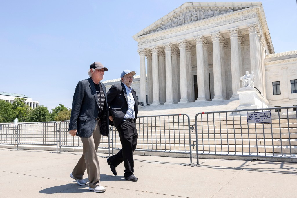 Ben Cohen (L) and Jerry Greenfield walk past the U.S. Supreme Court at an event where they gave out ice cream and called attention to police reform on May 20, 2021 in Washington, DC.
