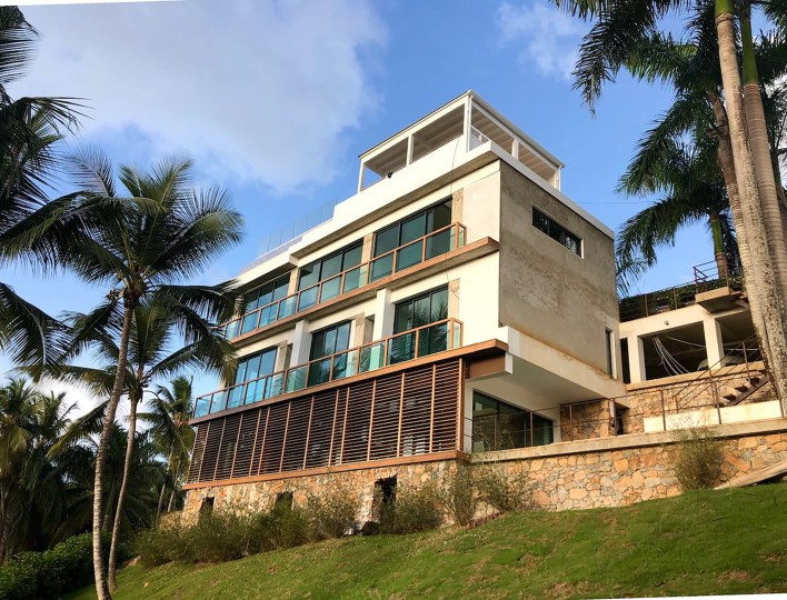 The gated, guarded four-story home is made of natural materials including wood, stones, rusted steel, brut concrete and coral stone, according to the listing.