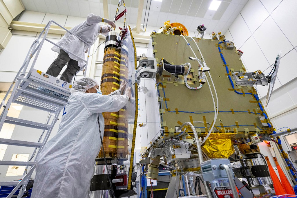 DART team members inspecting one of the spacecrafts that will be used in the launch.