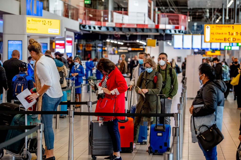 air travelers standing on line inside an airport terminal