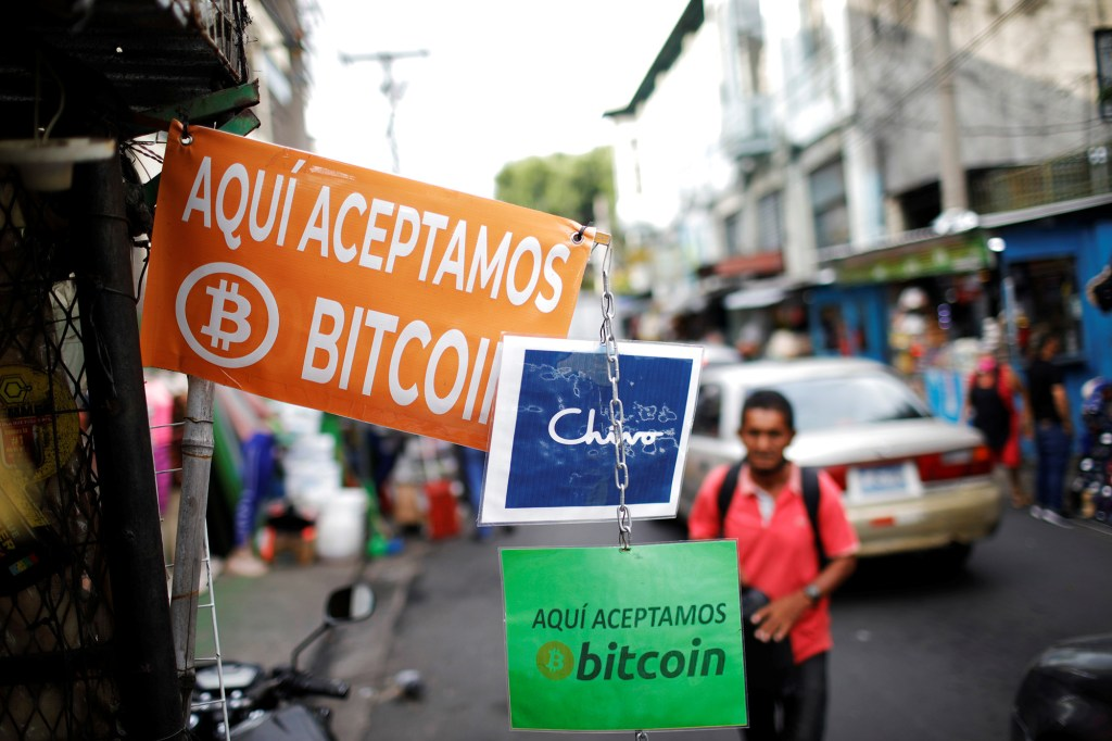 """A man walks past signs reading """"Bitcoin accepted here"""" outside a street stall where the cryptocurrency is accepted as a payment method in San Salvador, El Salvador October 4, 2021."""