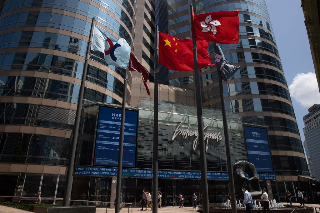 Pedestrians walk past a stock ticker outside Exchange Square, the building housing the Hong Kong Stock Exchange.
